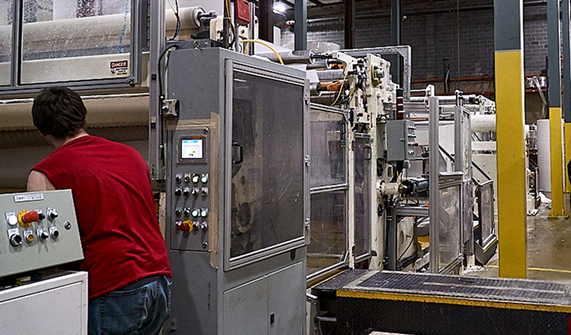 Factory worker assisting with production by using machinery